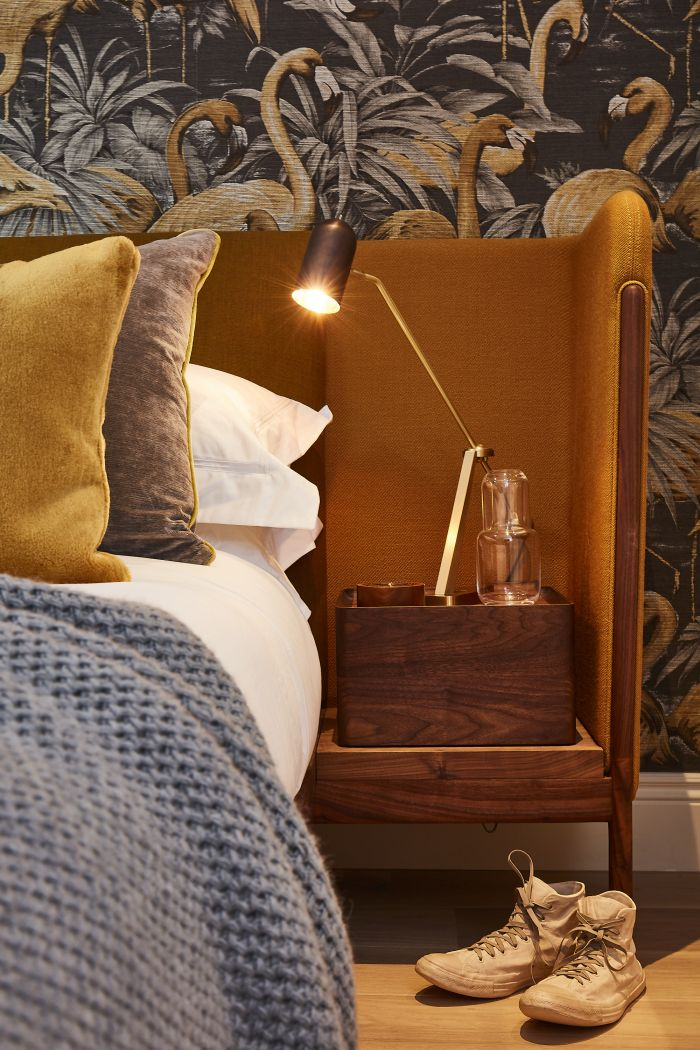 A stasis bedside lamp sits on top of de la espadea dubois bed in front of Arte International Wallcovering.