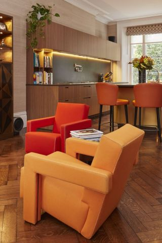A pair of orange armchairs seperate the boffi kitchen and dining area in this open plan kitchen living dining room.