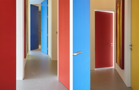 Colourful doors lead to different colour themed bedrooms off the central hallway.