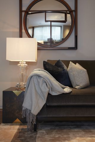 A corner of the living room showing a soft throw, mirror, side table and a lamp.