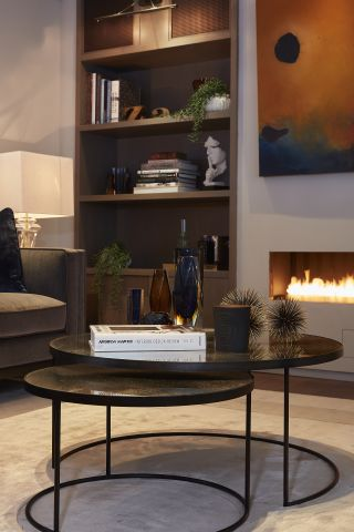 A set of nesting circular coffee tables on a rug in a living room with a lit fireplace.