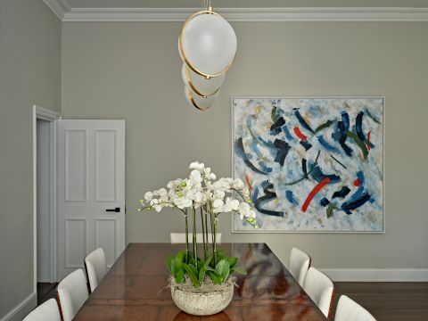 Dining room with baroncelli brass pendant lights and large oil painting on wall.