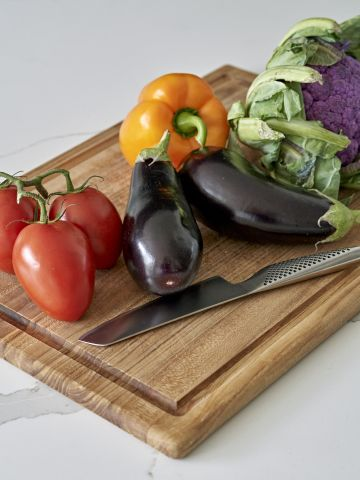 Fresh vegetables on a wooden chopping board with a global knife.