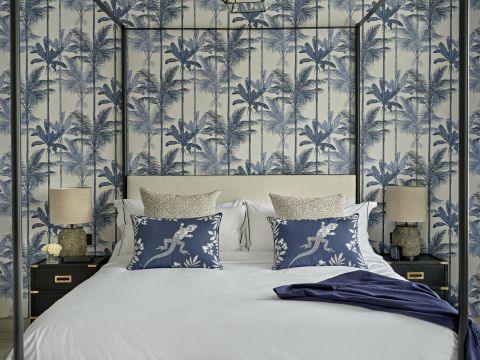 A luxury guest bedroom with four posted bed and blue Graham & Brown wallpaper.