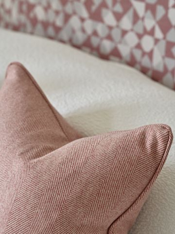 Layered cushions on a bed.